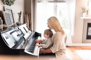 A mother teaching her child to play the piano - pack and move your piano safely
