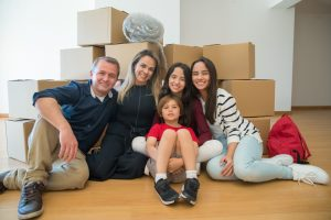 A family of 5 with moving boxes at the background - moving from Apex to Cary with kids